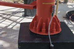 Винты и гайки на основании красного электрического столба от металла Стоковые Фото