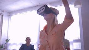 Виртуальная реальность, маленькая девочка в шлемофон VR играет современную игру с семьей в подсвеченном в комнате дома