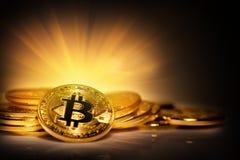 Виртуальное bitcoin валюты на куче разбросанных монеток в ярком Ра Стоковая Фотография