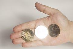 3 виртуальных bitcoins монеток держа руку Стоковые Фото