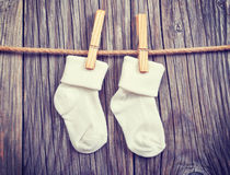 висеть товаров clothesline младенца Носки младенца белые на зажимке для белья Стоковые Фотографии RF