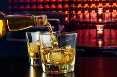 Виски бармена лить в Лаунж-баре стоковое изображение