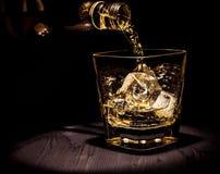 Виски бармена лить в стекле на деревянной таблице, теплой атмосфере, старом стиле, времени ослабляет с вискиом стоковое изображение