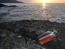 Виски в плоских бутылках на пляже утеса Стоковые Изображения RF