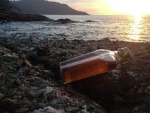 Виски в плоских бутылках на пляже утеса Стоковые Фото