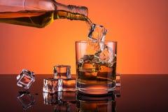 Виски лить от бутылки в стекло Стоковая Фотография