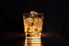 Виски с кубами льда в стекле на темном tabl предпосылки и древесины Стоковые Фото