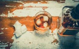 Виски с кубами льда, винтажное фото, бутылка вискиа Стоковые Изображения RF
