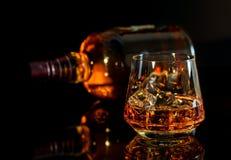 Виски с льдом в стекле и бутылке вискиа на черном backg Стоковое Фото