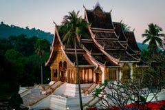 Висок в Luang Prabang небо получает красным на заходе солнца красивые золотые стены стоковое изображение