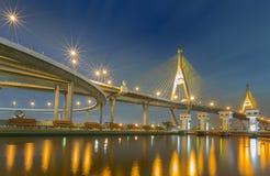 Висячий мост (мост Bhumibol) с уличным светом отражает в реке Стоковая Фотография RF