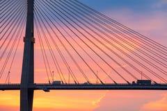 Висячий мост скрещивания тележки и грузового пикапа на заходе солнца col Стоковая Фотография