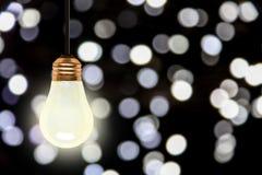Вися электрическая лампочка с предпосылкой светов Bokeh рождества стоковое фото rf