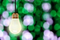 Вися электрическая лампочка с предпосылкой светов Bokeh рождества стоковые изображения