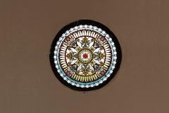 Витраж церков, метафоричный, круг красит стекло на конкретных коричневых обоях Стоковое Фото