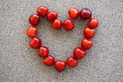 Вишни выровнялись в форме сердца на каменной предпосылке Стоковое Фото