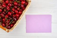 Вишни в карточке корзины и чистого листа бумаги Стоковое Фото
