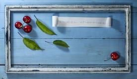 Вишни в старой рамке на голубой деревянной предпосылке Стоковые Изображения