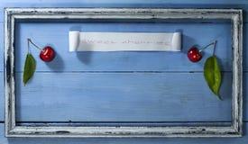 Вишни в старой рамке на голубой деревянной предпосылке Стоковые Фото