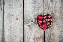 Вишни в в форме сердц шаре на деревенской деревянной предпосылке скопируйте космос Стоковые Изображения RF