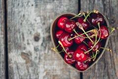 Вишни в в форме сердц шаре на деревенской деревянной предпосылке скопируйте космос Стоковые Фото