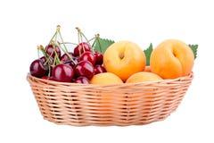 Вишни и абрикосы в деревянной корзине изолированной на белизне Стоковое Фото