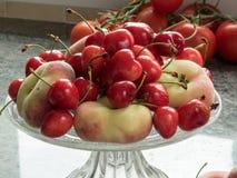 Вишни и персики в стеклянной чашке Стоковые Изображения RF