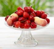 Вишни и персики в стеклянной чашке Стоковые Фото