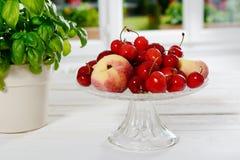 Вишни и персики в стеклянной чашке Стоковое Изображение