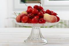 Вишни и персики в стеклянной чашке Стоковое Фото