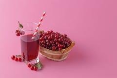 Вишни и стекло сока вишни на розовой предпосылке Стоковая Фотография