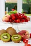 Вишни, кивиы и персики в стеклянной чашке Стоковое Изображение