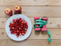 Вишни на гантелях яблок плиты красных и измеряя лента на w Стоковые Изображения
