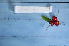 Вишни на голубой деревянной предпосылке Взгляд сверху Стоковая Фотография