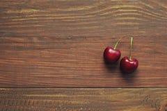 Вишни на деревянной предпосылке Стоковые Изображения RF