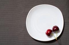 2 вишни на краю пустой плиты на предпосылке текстуры серой, космосе для текста, взгляд сверху Стоковое Изображение RF