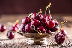 Вишни помадка вишен свежая Очень вкусные вишни с водой падают в ретро шар на старой таблице дуба стоковое фото rf
