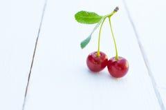 2 вишни с кабелем на деревянном столе Стоковая Фотография RF