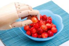 Вишня взятий деревянной руки простетическая от плиты на бамбуковой циновке при зрелые ягоды предусматриванные капельками воды Стоковые Фотографии RF