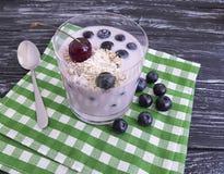 Вишня овсяной каши югурта, стекло голубики десерта на черной деревянной предпосылке Стоковое Изображение