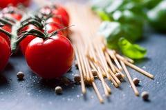Вишн-томаты, макаронные изделия спагетти, свежий базилик, специи на темной каменной предпосылке Стоковые Фотографии RF