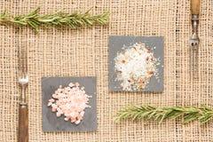 2 вида соли на темных плитах с вилками розмаринового масла и антиквариата Стоковое фото RF