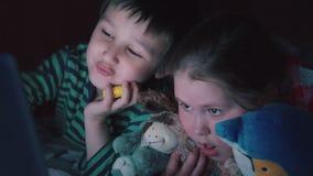Видео брата и сестры наблюдая на компьтер-книжке лежа на кровати в выравниваясь 4K акции видеоматериалы