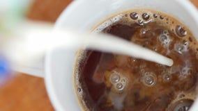 Видео замедленного движения лить молока потока в чашку кофе сток-видео