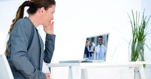 Видео конференц-связь коммерсантки с партнерами на компьютере Стоковые Изображения