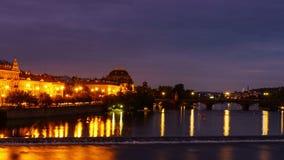 видео промежутка времени 4k реки Влтавы и театра Праги национального с мостом и светом отстает от автомобилей во время ночи в авг сток-видео