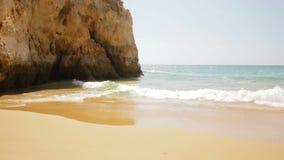 Видео пляжа волн вдоль желтого песка рядом с стороной скалы видеоматериал