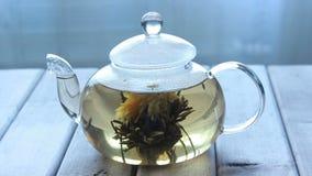 Видео стеклянного бака чая с чаем цветка китайским на деревянной предпосылке перед окном сток-видео