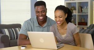 Видео счастливых черных пар смеясь над и наблюдая на компьтер-книжке стоковая фотография