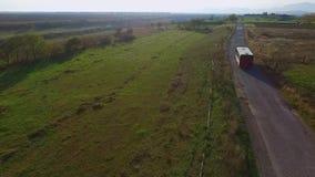 Видео трутня - повезите управлять на автобусе на сельской дороге - дорога через поле видеоматериал